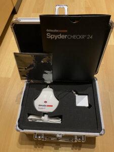 Der - auf dem Boden abgestellte - aufgeklappte Aluminiumkoffer, der den datacolor Spyder X mit USB-Kabel zum Monitor kalibrieren und den Spyder Cube, einen Würfel zum Weißabgleich mit weißen, grauen und schwarzen Flächen in Schaumstoff gebettet enthält. Sowie dem Spyder Checkr24, einer Farbtafel mit 24 Farben.